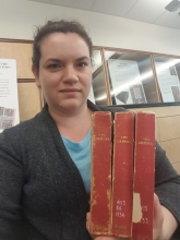 Caroline Winter, the editor of Mary Shelley's Gothic Tales in <em>The Keepsake</em>, holds three volumes of the annual in the University of Victoria Libraries Special Collections reading room.